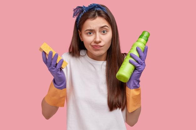 Concept de ménage et de nettoyage. malheureuse jeune concierge confuse aux cheveux longs, tient une éponge et une bouteille verte avec un détergent, porte des gants en caoutchouc pour la protection des mains, fait les tâches ménagères