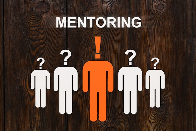 Concept de mentorat. hommes de papier sur bois.