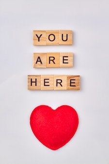 Concept de message d'amour. vous êtes ici écrit avec des blocs de bois. coeur rouge isolé sur fond blanc.
