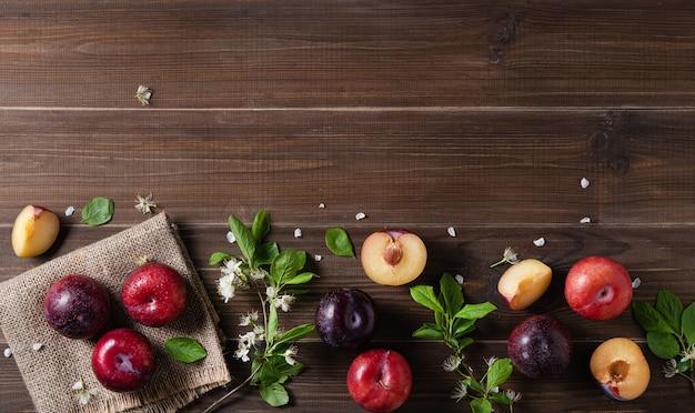 Le concept met à plat quelques prunes rouges juteuses avec des fleurs de branche sur un fond de bois brun. vue de dessus et copie de l'image de l'espace
