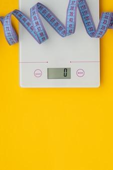 Concept mince. échelle et ruban à mesurer sur fond jaune vif