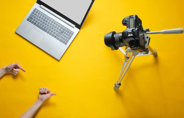 Concept minimal de blog. j'aime et abonnement. les mains féminines bloguent avec l'appareil photo sur un trépied et un ordinateur portable. vue de dessus