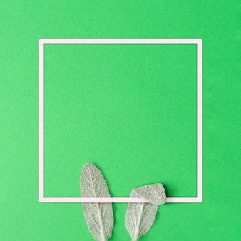 Concept minimal de joyeuses pâques. oreilles de lapin faites de feuilles vertes naturelles sur vert.