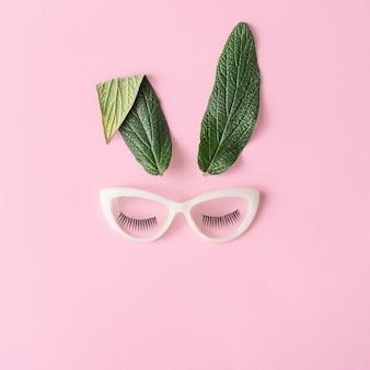 Concept minimal de joyeuses pâques. visage de lapin fait de feuilles vertes naturelles avec des lunettes sur rose pastel.