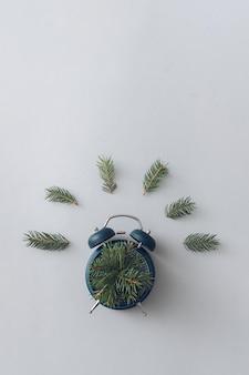 Concept minimal moderne de réveil et de branches de pin. mise à plat. notion de nature.