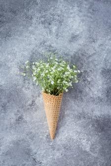 Concept minimal de printemps. cône de gaufre avec des fleurs de gypsophile