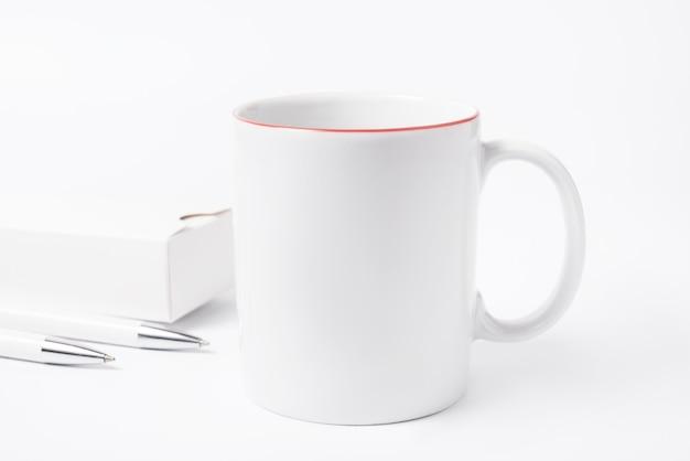Concept de minimalisme, tasse à café et crayons sur un bureau blanc