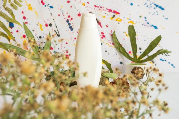 Concept minimaliste. bouteilles cosmétiques sur fond abstrait avec décoration de fleurs et de feuilles séchées