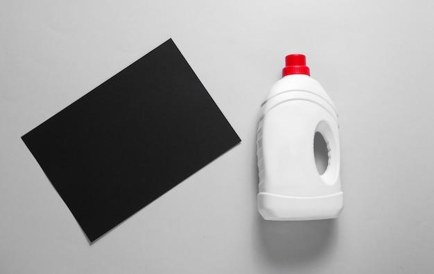 Concept minimaliste de lavage. feuille de papier noir pour l'espace de copie, bouteille de gel lavant sur table grise. vue de dessus