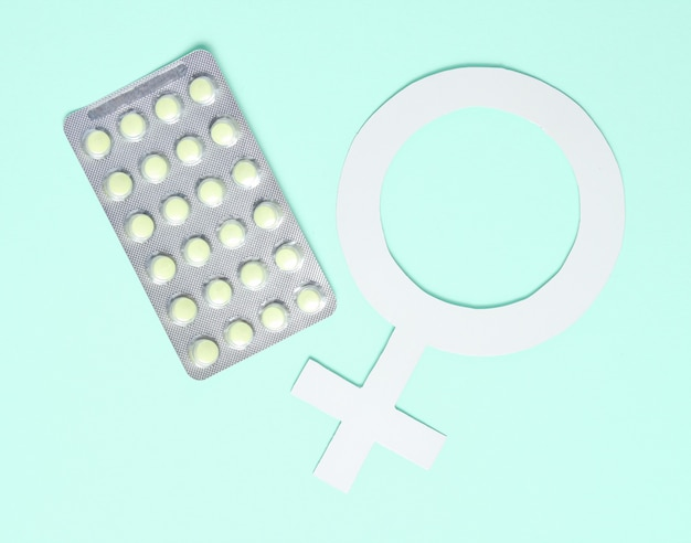 Concept minimaliste de médecine féminine. pilules, symbole de sexe féminin sur fond bleu.