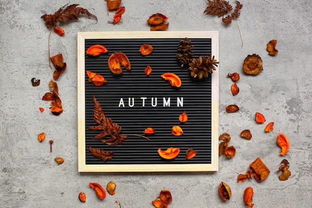 Concept minimaliste à plat d'automne avec tableau à lettres et feuilles sèches sur fond de ciment gris