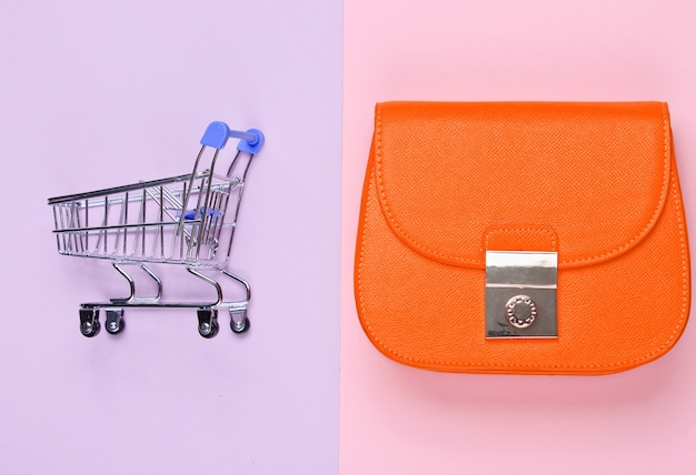 Concept minimaliste shopaholic. sac jaune, mini caddie sur fond pastel. vue de dessus