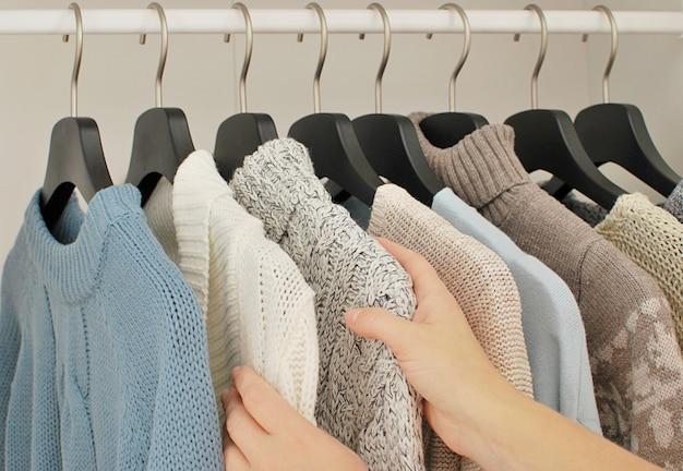 Concept de mode automne - hiver. femme choisissant des tricots chauds.