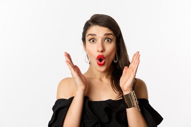 Concept de mode et de beauté. gros plan d'une femme excitée avec du maquillage et du rouge à lèvres, l'air surpris et heureux, debout sur fond blanc.