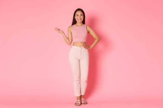 Concept de mode, de beauté et de style de vie. superbe femme asiatique en tenue élégante, souriant largement comme démonstration de produit vers la gauche, levant le bras, pointant ou montrant quelque chose, publicité