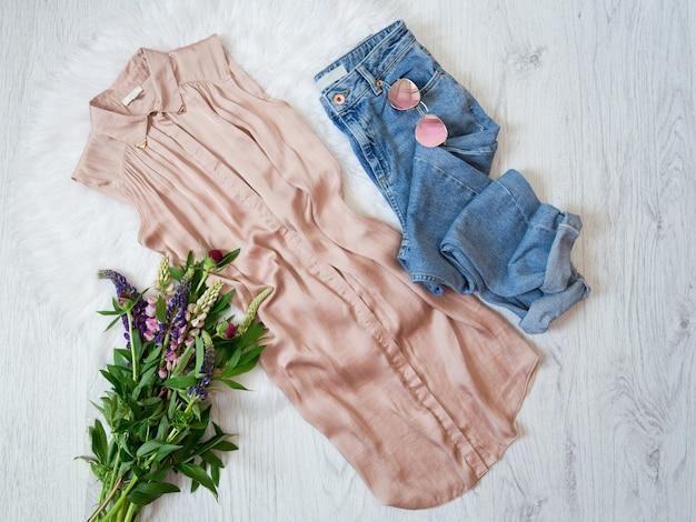 Concept à la mode. blouse beige, jeans, lunettes et bouquets de fleurs.