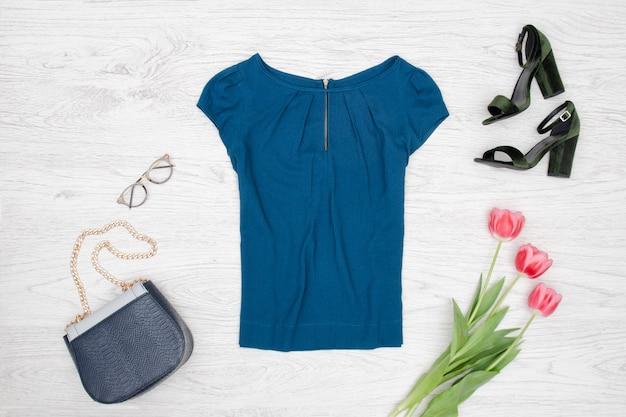 Concept de mode blouse bleue, sac à main, lunettes, chaussures noires et tulipes roses. vue de dessus