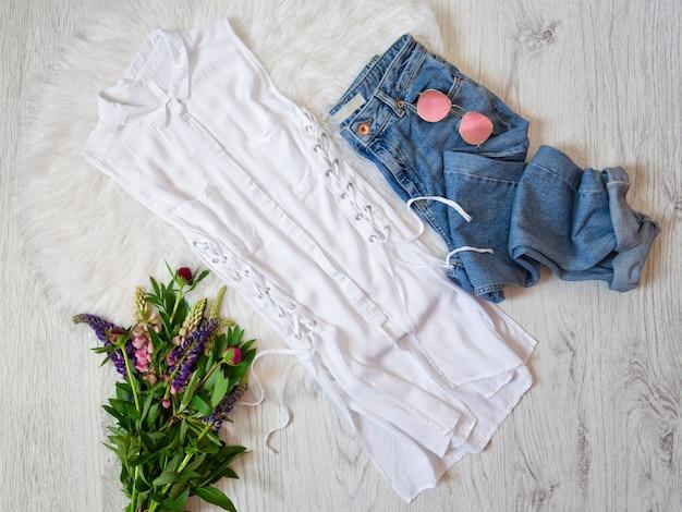 Concept à la mode. chemisier blanc avec cravates, jeans, lunettes et bouquets de fleurs.