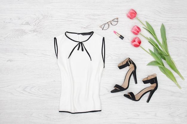 Concept de mode chemisier blanc, lunettes, rouge à lèvres et tulipes roses. vue de dessus