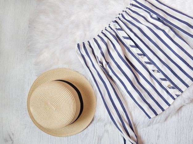 Concept à la mode. chemisier à rayures blanches et chapeau sur fourrure blanche