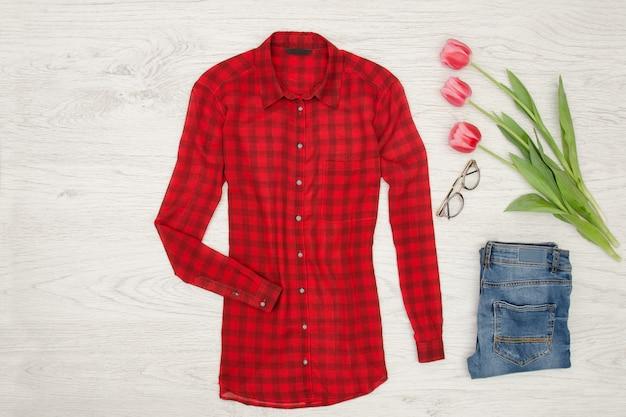 Concept de mode chemisier rouge, jeans, rouge à lèvres et tulipes roses. vue de dessus