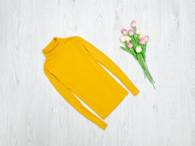 Concept de mode. col roulé jaune et tulipes roses. fond bois
