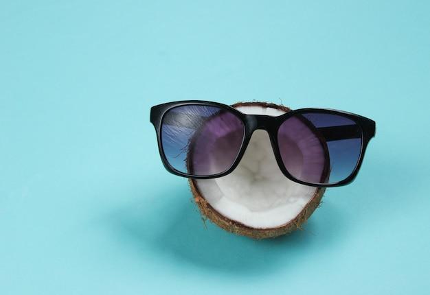 Concept de mode créatif. la moitié de la noix de coco avec des lunettes de soleil sur fond bleu