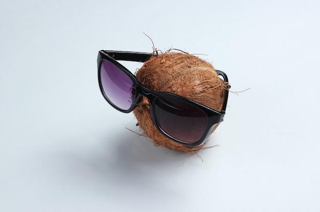 Concept de mode créatif. noix de coco avec des lunettes de soleil sur fond blanc