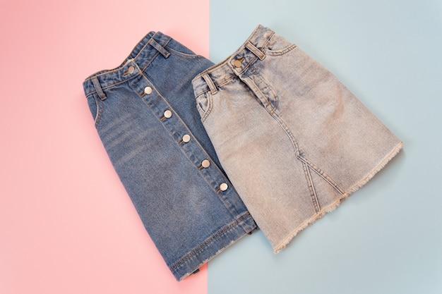 Concept à la mode. deux jupes en jean, bleu et gris. fond rose et bleu tendre.