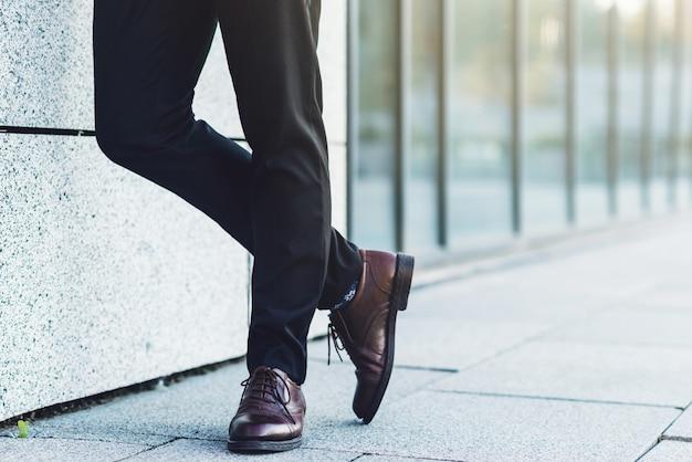 Concept de mode d'entreprise masculine. l ¡desserrage des jambes d'un homme dans un pantalon de travail et des chaussures près du mur