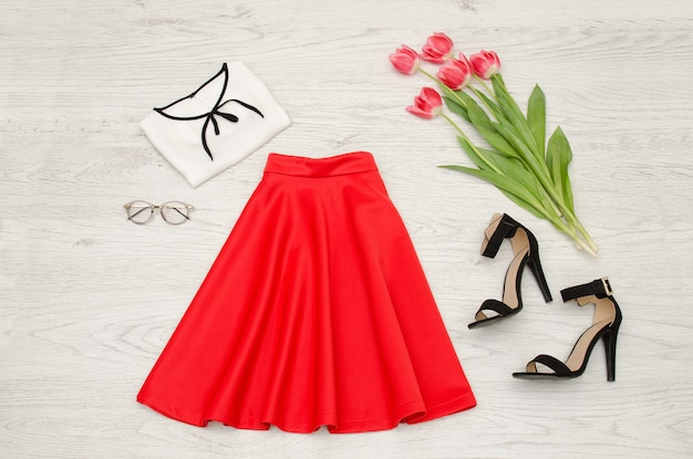 Concept de mode jupe rouge, chemisier, lunettes de soleil, rouge à lèvres, chaussures noires et tulipes roses. vue de dessus
