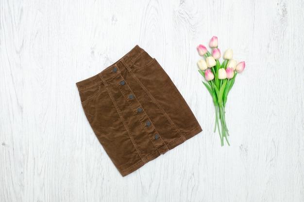 Concept de mode. jupe en velours marron et tulipes roses. fond bois