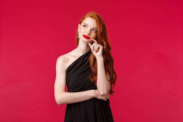 Concept de mode, luxe et beauté. portrait de rêveuse jeune femme rousse élégante et sensuelle avec rouge à lèvres, maquillage de soirée, porter une robe noire luxueuse, chercher comme rêver ou imagerie