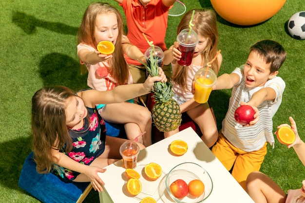 Concept de mode pour enfants. le groupe d'adolescents garçons et filles assis sur l'herbe verte au parc. vêtements colorés pour enfants, style de vie, concepts de couleurs à la mode.