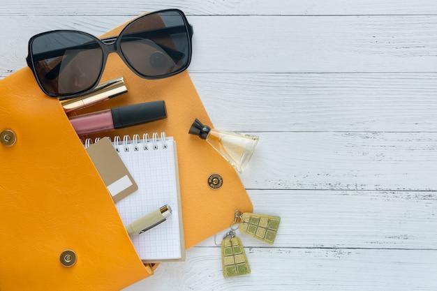 Concept de mode produits cosmétiques, lunettes de soleil, ordinateur portable et sac à main orange.