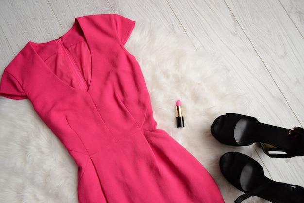 Concept de mode. robe rose vif, rouge à lèvres et chaussures noires à fourrure blanche.