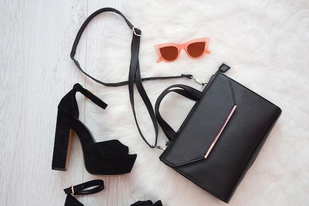Concept de mode. sac à main noir, chaussures et lunettes roses sur fond blanc.