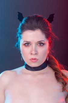 Concept de mode sombre, halloween et personnes - femme gothique en oreilles de chauve-souris sur le mur sombre