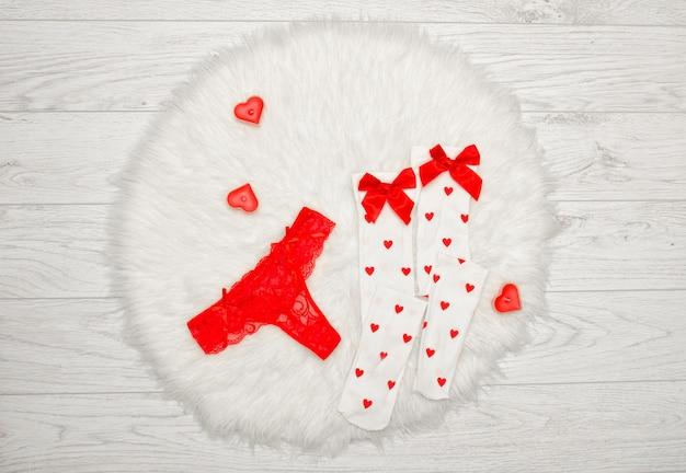Concept de mode string rouge et bas blancs avec des arcs, des bougies en forme de coeur sur une fourrure blanche