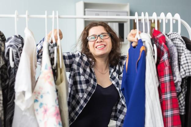Concept de mode, de style et de personnes - femme choisissant des vêtements devant un placard complet