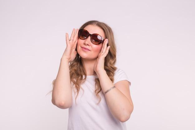 Concept de mode, de style et de personnes - jolie jeune femme portant des lunettes de soleil sur une surface blanche