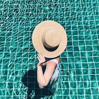 Concept de mode et de vacances de voyage d'été. belle jeune femme bronzée avec un chapeau de paille et un maillot de bain blanc est debout à la piscine