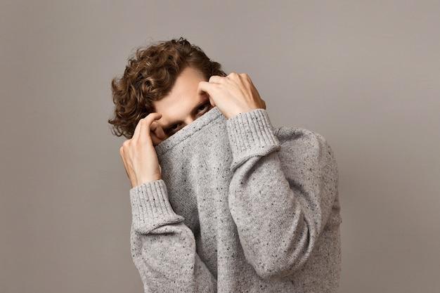 Concept de mode, vêtements, vêtements, style et personnes pour hommes. image isolée horizontale de beau jeune homme confiant avec des cheveux roux bouclés se cachant sous un pull élégant, ayant un regard mystérieux