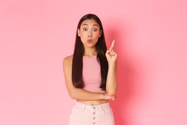 Concept de mode de vie, de beauté et de femmes. une jolie fille asiatique créative en vêtements d'été a une solution, en levant l'index et en disant son idée, en imaginant un bon plan, un mur rose debout