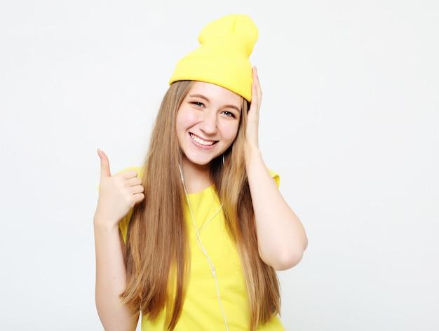 Concept de mode de vie, d'émotion et de personnes: femme heureuse portant des vêtements jaunes, abandonnant le pouce
