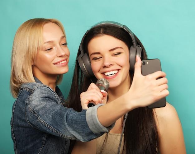 Concept de mode de vie, d'émotion et de personnes. heureux jeunes filles avec microphone prendre une photo avec smartphone sur bleu