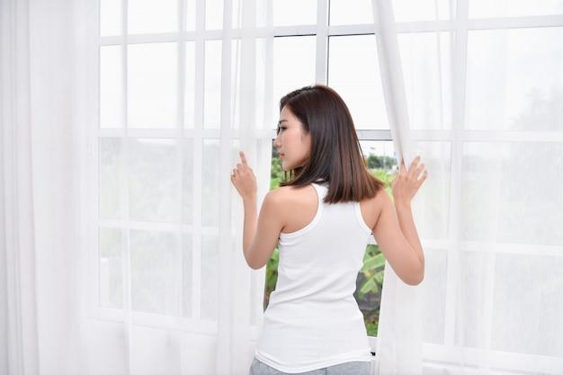Concept de mode de vie. les filles asiatiques sont réveillées. belle femme asiatique se détend dans une chambre blanche.