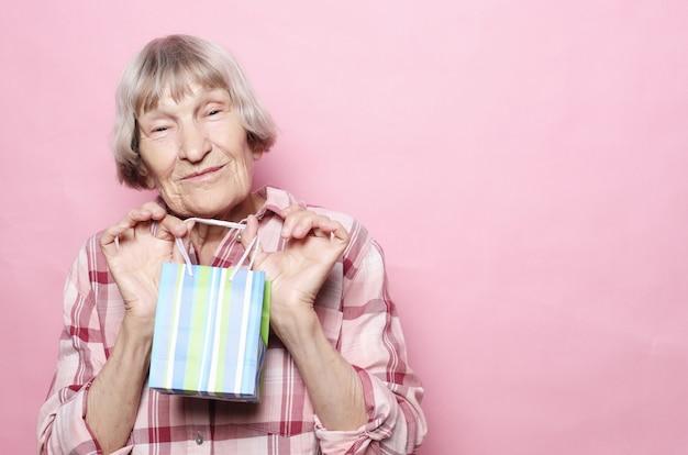 Concept de mode de vie et les gens: heureuse femme senior avec sac à provisions sur fond rose