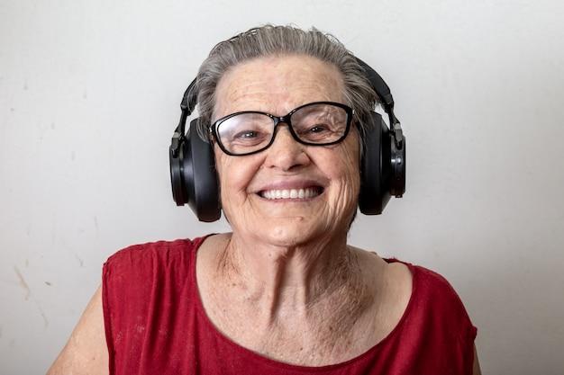Concept de mode de vie et les gens: vieille dame drôle, écouter de la musique et danser sur fond blanc. vieille femme portant des lunettes dansant sur de la musique, écoutant sur ses écouteurs.