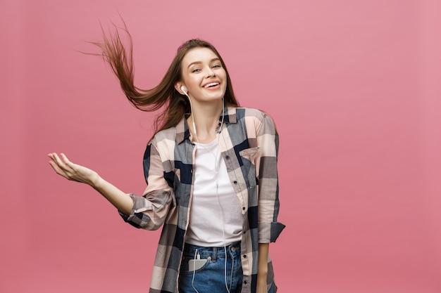 Concept de mode de vie. jeune femme à l'aide de téléphone pour écouter de la musique sur fond rose.